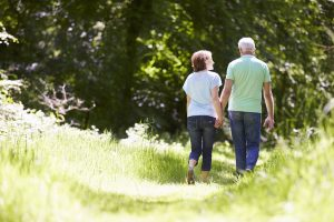 Middle-aged couple walking through countryside, viewed from behind
