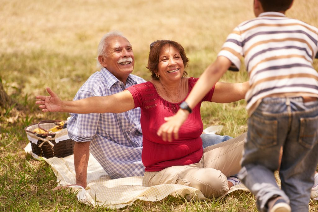 child running toward grandparents for a hug, picnic outdoors