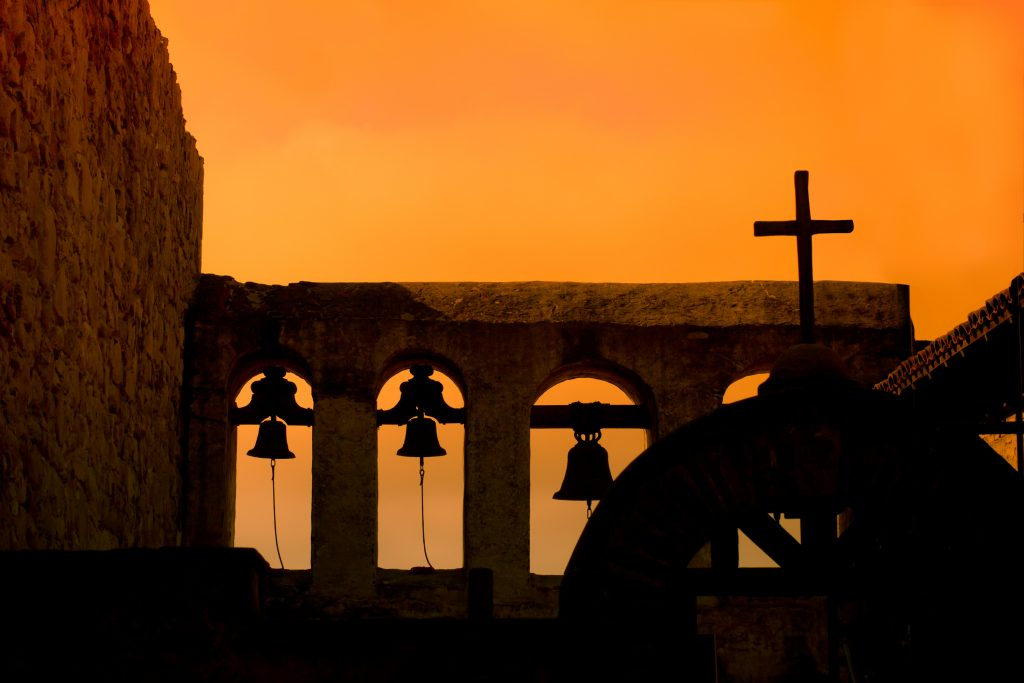 Church bells and cross against a dawn sky