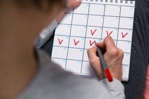 woman checking periods on menstrual calendar