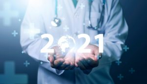 Doctor in lab coat holding in his hands glowing 2021 with globe